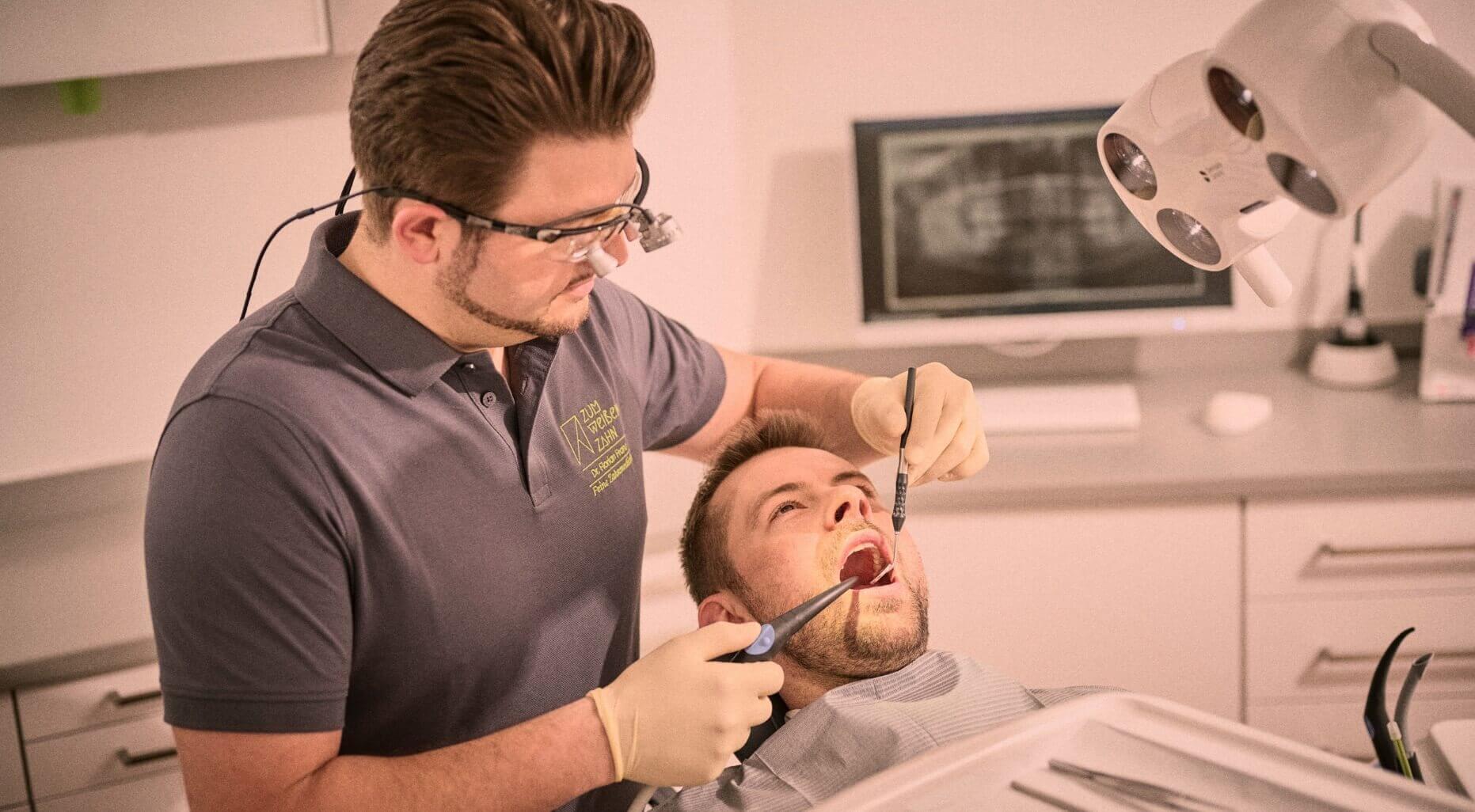 Zahnarzt Dr. Franz bei einer Behandlung in der Zahnarztpraxis Zum weißen Zahn in Nürnberg